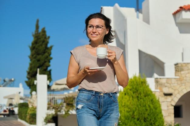 カップと歩いて成熟した美しい女性の屋外のポートレート