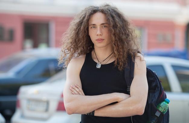 現代の若い男の屋外のポートレートは、通りを歩きます。長い巻き毛を持つ男。