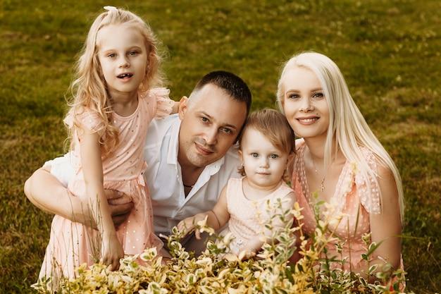2人の幼い娘が屋外にいる母と父の屋外の肖像画。カメラの笑顔を見ながら子供たちを抱きしめるママとパパ。