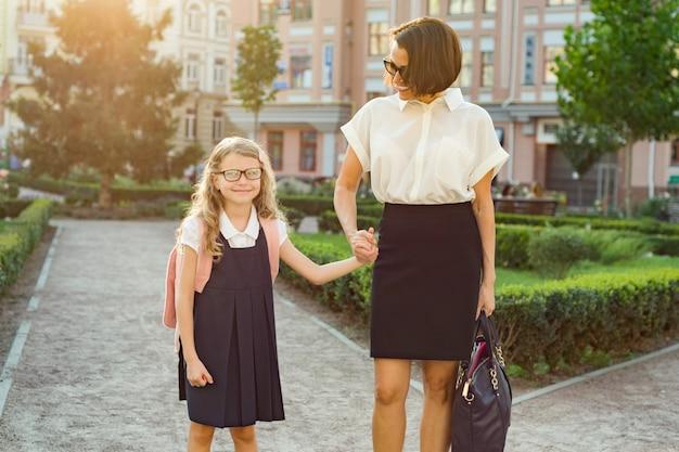 親と子の学校への道の屋外のポートレート