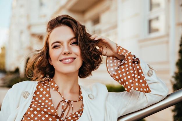 ぼやけた街で満足しているブルネットの女性の屋外の肖像画。トレンディなヘアカットで白人の魅惑的な女の子のショット。