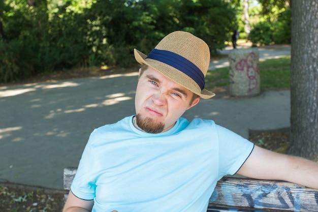 공원 슬픔과 실망 개념에 벤치에 앉아 슬픈 젊은 남자의 야외 초상화