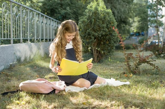 ノートを読んで草の上に座っている女子高生の屋外のポートレート