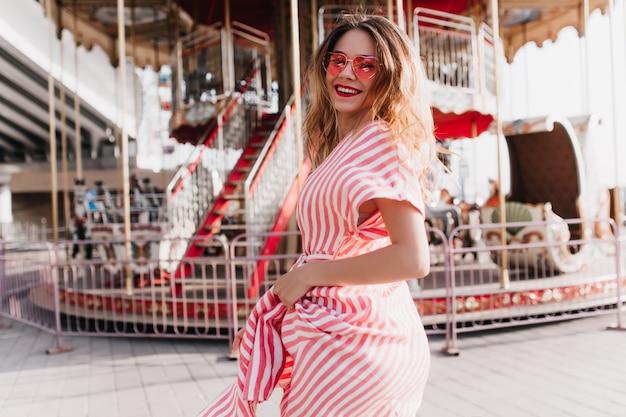 놀이 공원에서 포즈를 취하는 여름 복장에 매끈한 백인 여자의 야외 초상화. 회전 목마 근처에 서서 그녀의 어깨 너머로보고 분홍색 선글라스에 만족 된 여성 모델.
