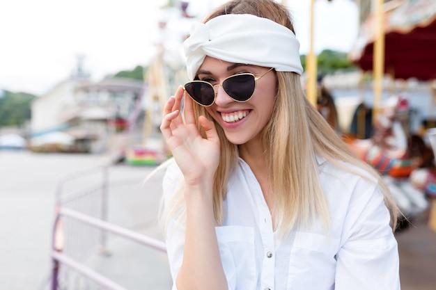 黒のサングラスをかけた見事なヨーロッパの女性の屋外の肖像画は、公園のアトラクションで自由な時間を過ごす白い服を着ています。ヘアアクセサリーと白いシャツの素敵な女の子は夏休み中に楽しんでいます
