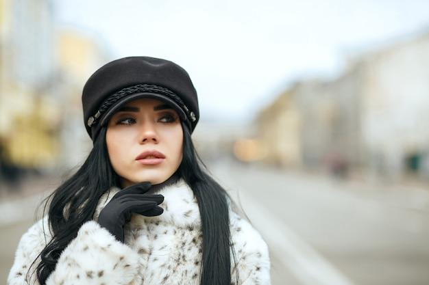 スタイリッシュな黒のキャップと暖かいコートを着ている見事な女の子の屋外の肖像画。テキスト用のスペース