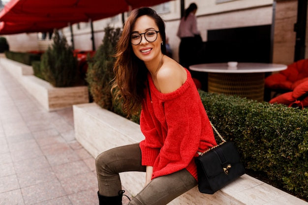 座っているとヨーロッパの休日を楽しんでいるトレンディな赤いニットセーターで成功した笑顔ブルネットの女性の屋外のポートレート。エレガントな黒のバッグ。