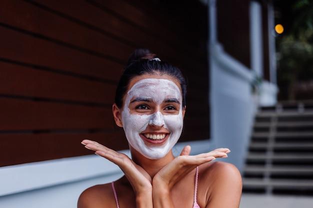顔に白いピーリングマスクとスパでビキニで日焼けした肌の穏やかなかなり白人女性の屋外の肖像画