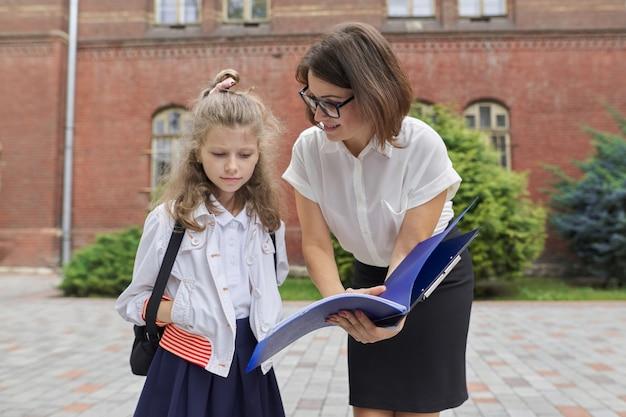 교사 여자와 함께 작은 학생 여자의 야외 초상화. 학교 건물 근처 아이 학습 서류를 보여주는 교사. 다시 학교로, 수업 시작