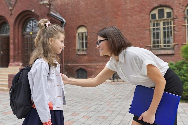 一緒に先生の女性と小さな学生の女の子の屋外の肖像画。