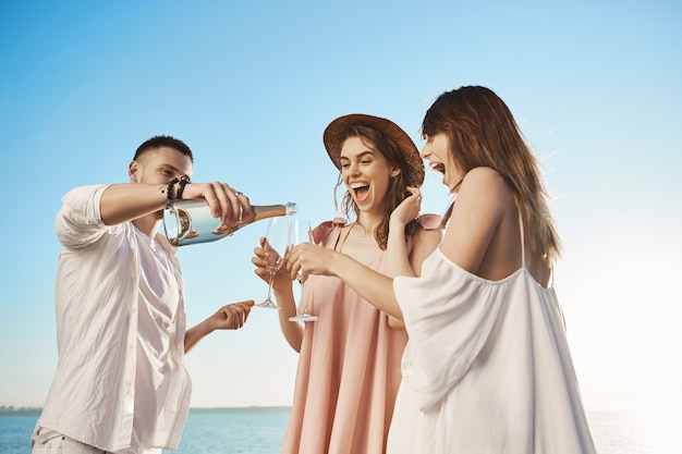 샴페인을 마시고 해변에서 쉬고있는 동안 광범위하게 웃고 세 젊은 성인의 야외 초상화. 잘 생긴 수염 난 남자가 친구 안경에 술을 마시고 행복한 미래를 응원합니다.