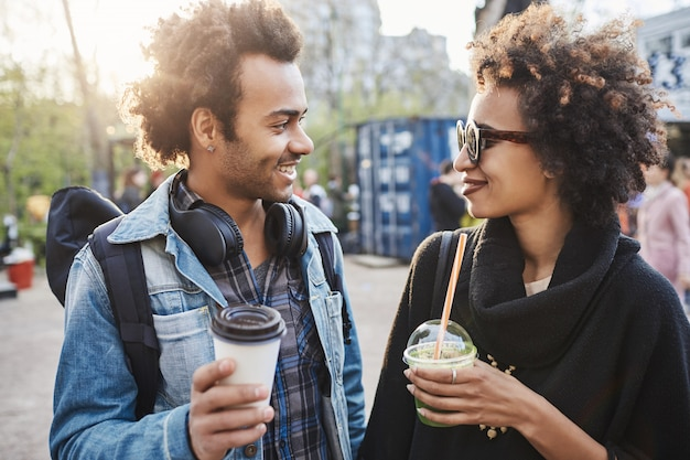 公園の周りにぶら下がって、コーヒーを飲みながら、笑って話している2人のかわいいアフリカ系アメリカ人の屋外のポートレート。