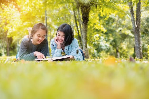 2つのかわいい女の子の本を読んでいる屋外肖像画