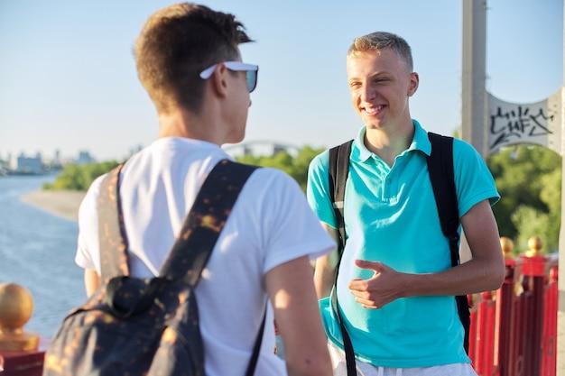 Открытый портрет двух друзей мальчиков-подростков 15, 16 лет, говорящих смеясь. ребята стояли на мосту через реку в солнечный летний день. молодость, дружба, общение