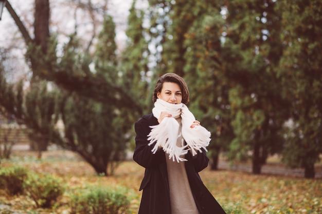 겨울 검은 코트와 흰색 스카프를 착용 공원에서 여자의 야외 초상화
