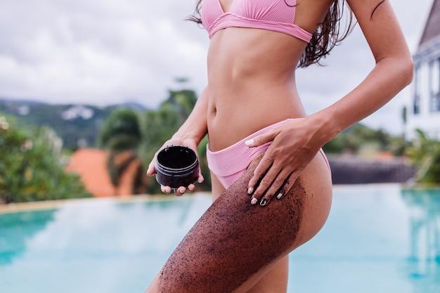 Открытый портрет женщины в розовом бикини в спа-салоне у бассейна, держащей кофейный скраб