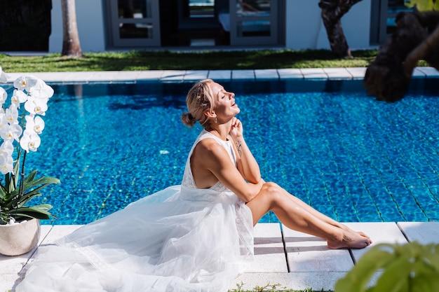 花蘭と青いプールの近くに座っている白いウェディングドレスの女性の屋外の肖像画