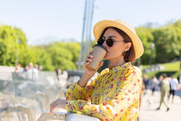 太陽を楽しんでいるコーヒーのカップと黄色の夏のドレスと帽子の女性の屋外の肖像画は、街の素晴らしい景色と橋の上に立っています