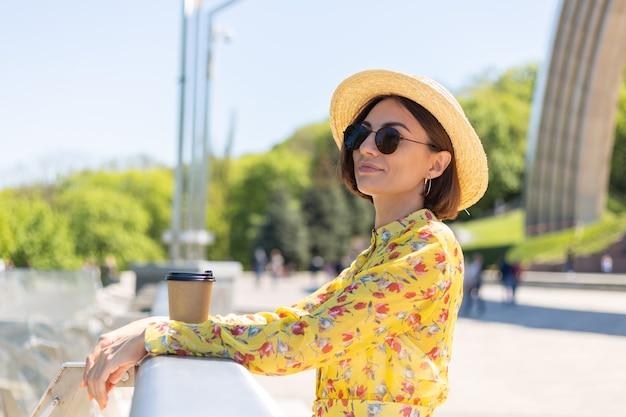 태양을 즐기는 커피 한잔과 함께 노란색 여름 드레스와 모자에 여자의 야외 초상화, 도시 놀라운 볼 수있는 다리에 서