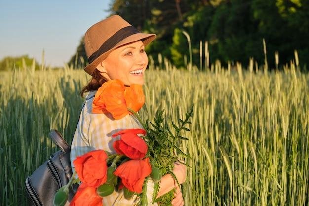 赤いケシの花束を持つ女性の屋外のポートレート