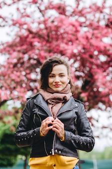 花木の近くポーズ若い美しいファッショナブルな女性の屋外のポートレート。女性の美しさとファッション。シティライフスタイル。黄色のカーディガンピンクの花盛りの木の女の子。