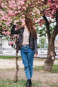 Внешний портрет молодой красивой модной дамы представляя около цветя дерева. женская красота мода. городской образ жизни. девушка в желтый кардиган розовые цветущие деревья. девушка улыбается