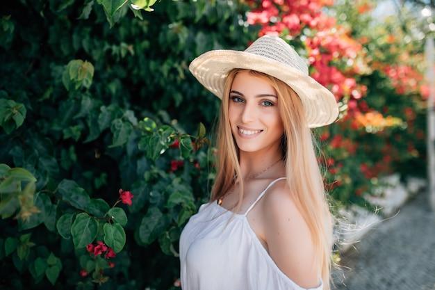 Открытый портрет молодой красивой счастливой улыбающейся дамы, позирующей возле цветущего дерева. городской образ жизни