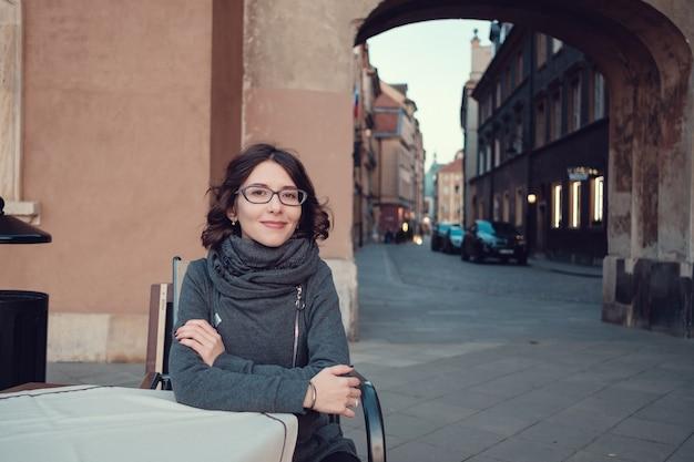 古い通りでポーズをとって若い美しい女性の屋外の肖像画。