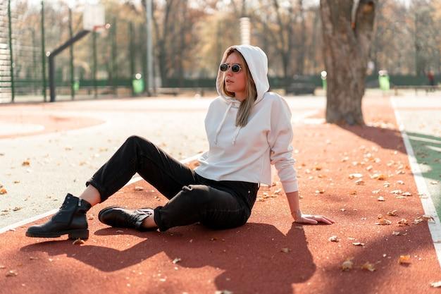 スポーツグラウンドのトラックに座っているサングラスと白いフード付きセーターを着た若い美しい女性の屋外の肖像画。若者文化夏の娯楽