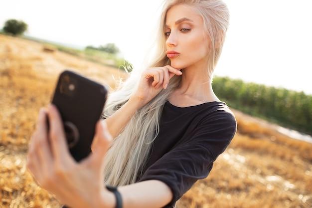 スマートフォンでselfieを取る若い美しさのブロンドの女の子の屋外の肖像画。