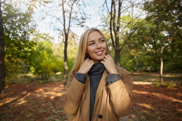 若い金髪の女性の屋外の肖像画は、公園を散歩しながら脇に見えます。