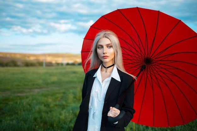 Открытый портрет молодой блондинки, держащей красный зонтик, в черном костюме. предпосылка облачного неба и зеленого поля.