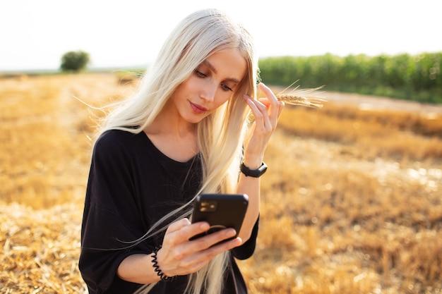 スマートフォンを手に、フィールドで若いブロンドの女の子の屋外の肖像画。