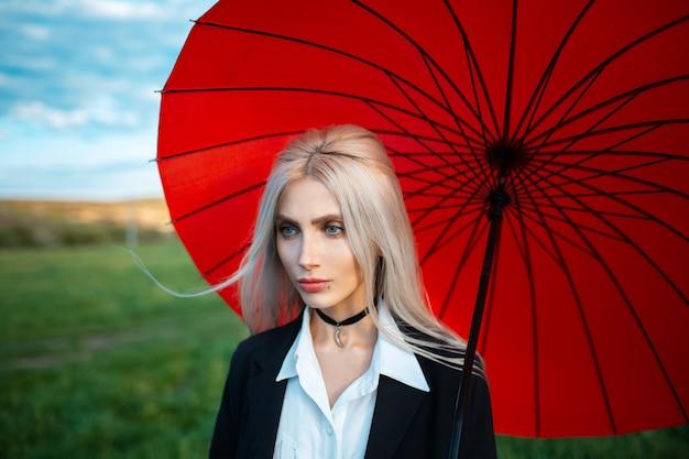 Открытый портрет молодой блондинки красивой девушки, держащей красный зонтик, в черном костюме. предпосылка облачного неба и зеленого поля.
