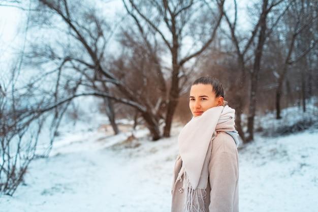 나무의 배경에 스카프와 코트를 입고 겨울 날에 공원에서 젊은 여자의 야외 초상화.
