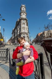 彼の小さな幼児を保持している若いredhaired父親の屋外の肖像画