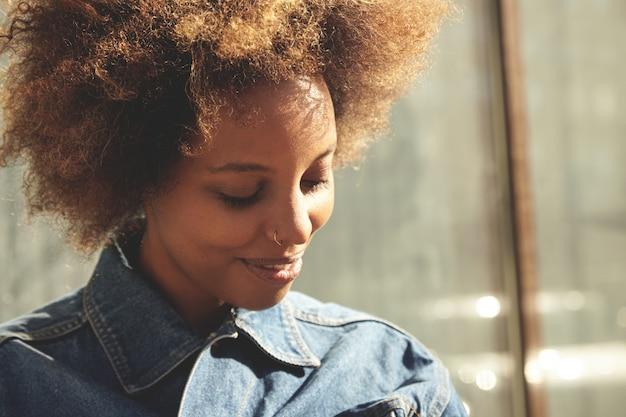 デニムジャケットを着ている巻き毛を持つ若いスタイリッシュな浅黒い女性の屋外のポートレート