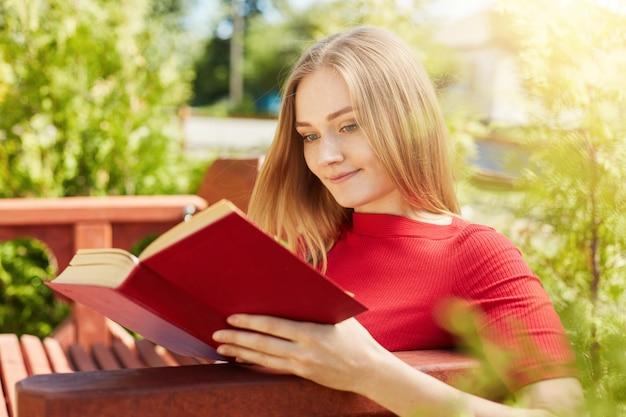 Открытый портрет молодой девушки со светлыми волосами, одетый в красную блузку, сидя на деревянной скамейке