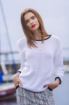 海のセーターと海のヨットの前でポーズをとって青いズボンを着た若い女性の屋外のポートレート。