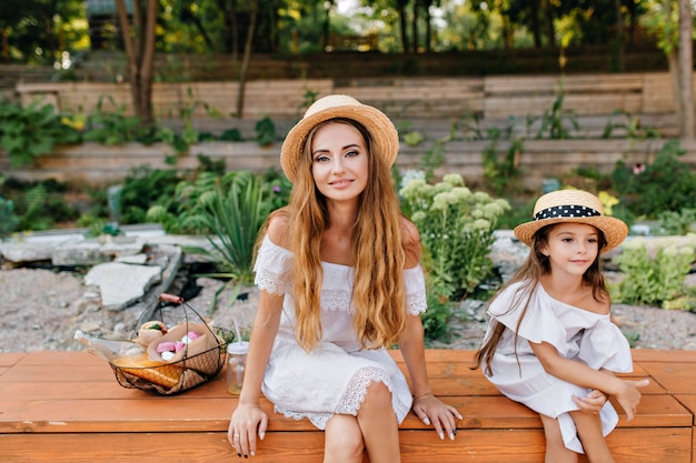 Outdoor portrait of pleased young woman and girl sitting with legs crossed in park on nature after picnic. photo of charming lady with basket of food spending time with daughter in garden.
