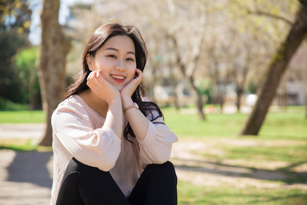 Outdoor portrait of positive smiling asian student girl