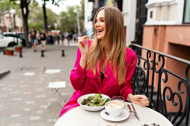 Outdoor portrait of pretty stylish blonde woman enjoying her healthy vegetarian bowl on city terrace, tasty lunch, stylish clothes.