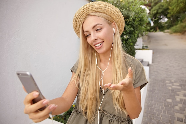 Outdoor portrait of pretty young woman with long blond hair communicating with friend by video, using smartphone and headphones, wearing casual linen dress and straw hat
