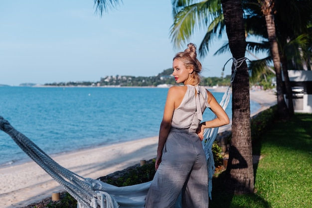 Outdoor portrait of rich caucasian woman in classic jumpsuit with red lipstick by hammock on vacation outside villa hotel
