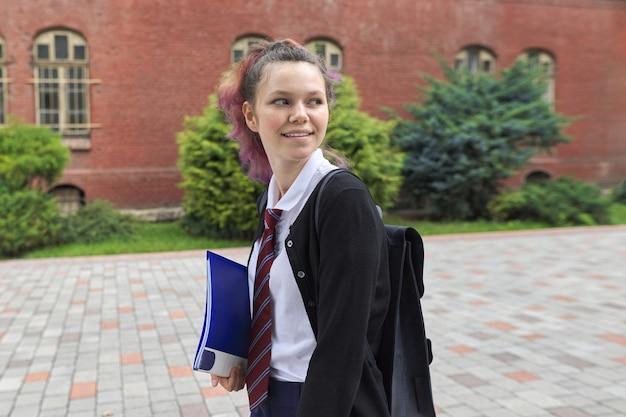 Outdoor portrait of schoolgirl near school building, beautiful trendy teenager girl with backpack going school