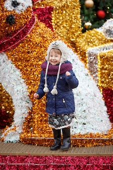 Outdoor portrait of smiling little girl in christmas decorations on street of european city