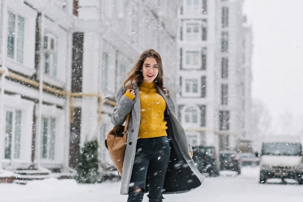 Outdoor portrait of spectacular lady in yellow sweater walking down the street in warm winter day. photo of pleased fashionable woman in gray coat standing under snowfall on urban street.