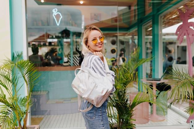 Ritratto all'aperto della donna graziosa alla moda che indossa la camicia spogliata e gli occhiali arancioni rotondi