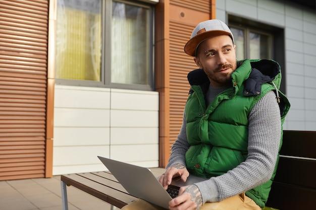 Ritratto all'aperto di elegante freelance maschio con la barba lunga in abiti alla moda seduto su una panchina con il computer portatile sulle ginocchia, utilizzando la connessione internet wireless 4g per il lavoro online, la tastiera