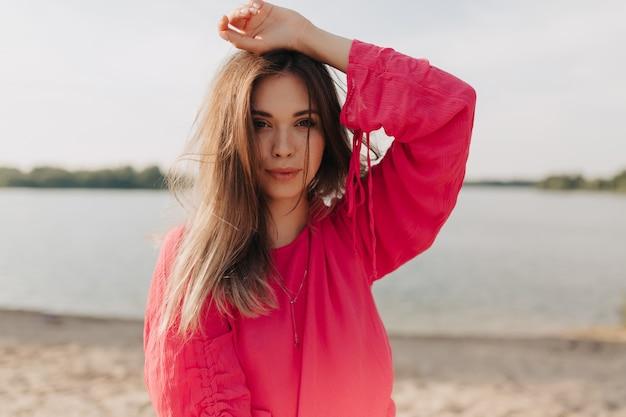Outdoor ritratto di donna alla moda in abito rosa in posa all'aperto nel giorno d'estate